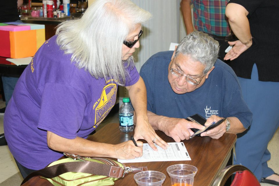 A woman with white hair and purple shirt assists a man with a blue shirt and glasses in writing down something.