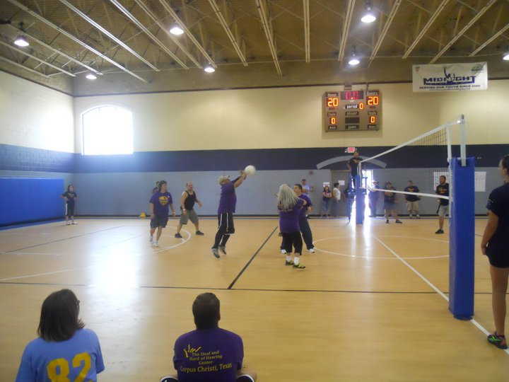 A volleyball game is playing in a gym of tan floors, blue and tan walls.