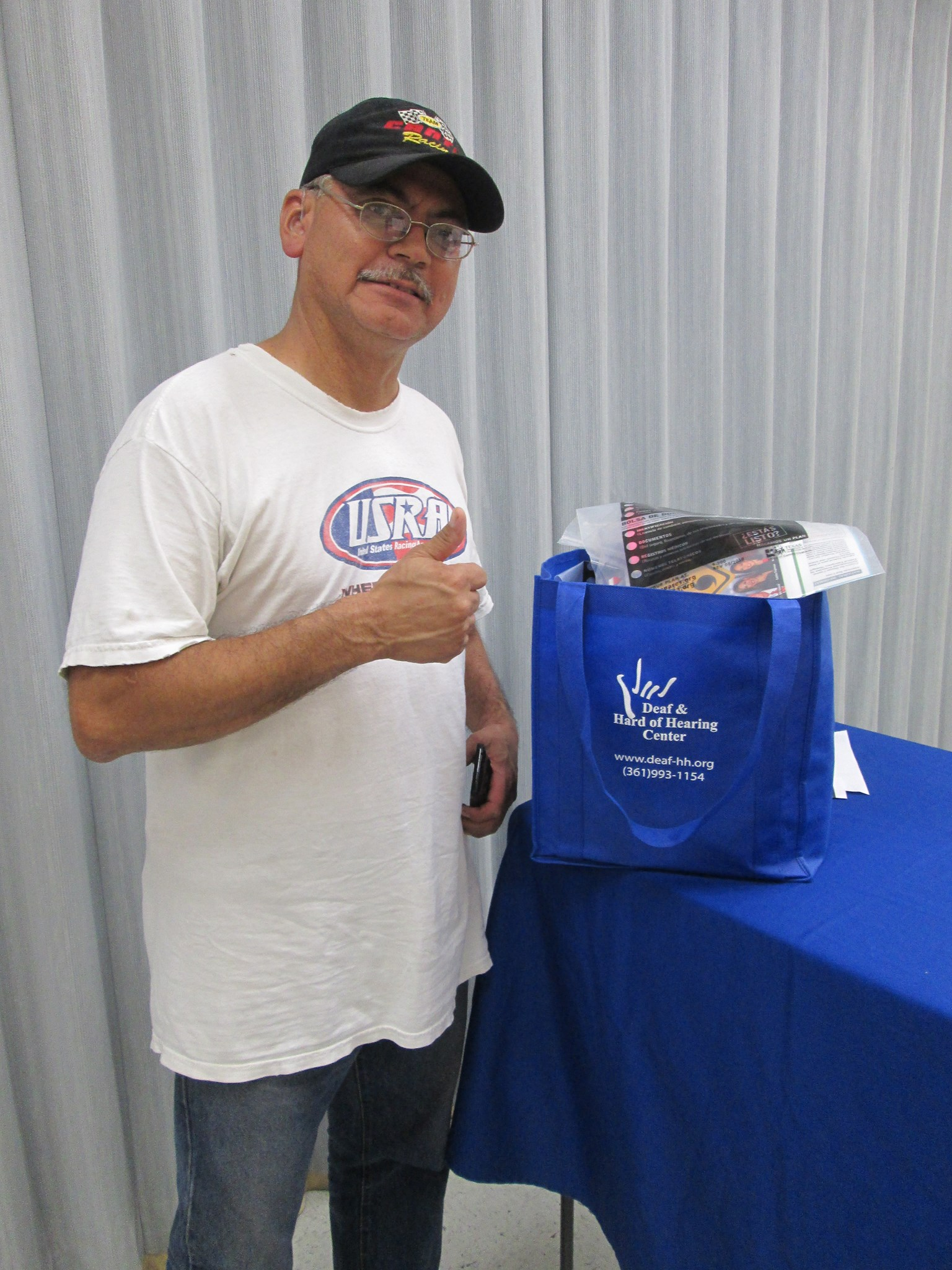 A male looks at the camera with a thumbs up. Next to him is a bag of goodies on a blue table.