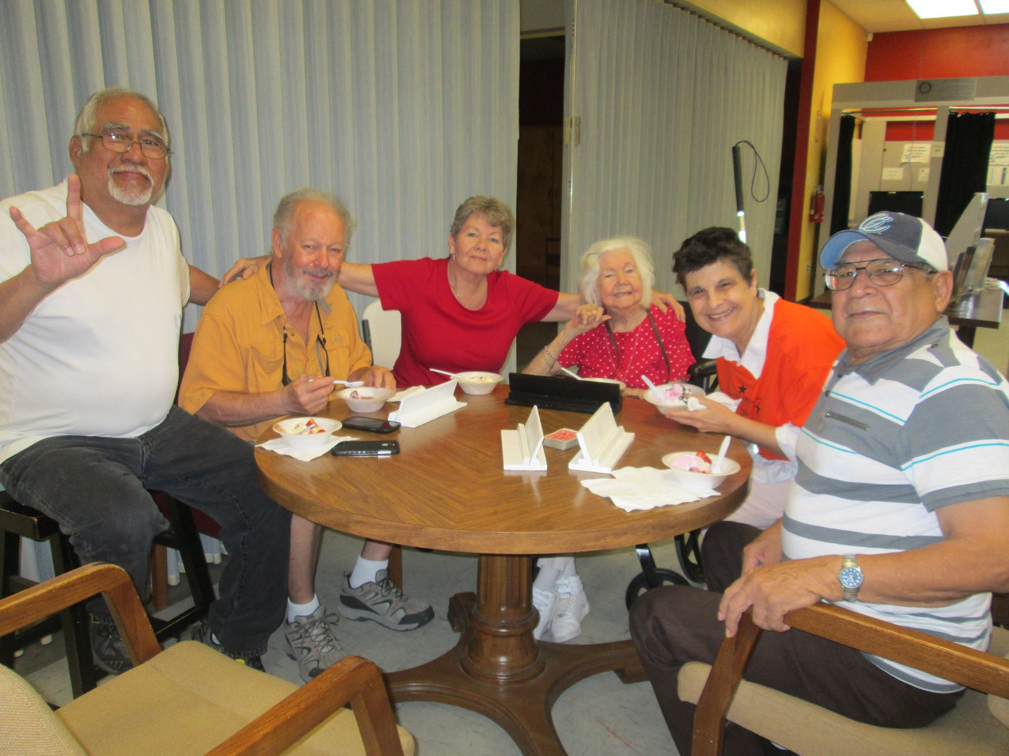 """Six senior citizens sit around a round table and smile at the camera. One is signing """"I love you""""."""
