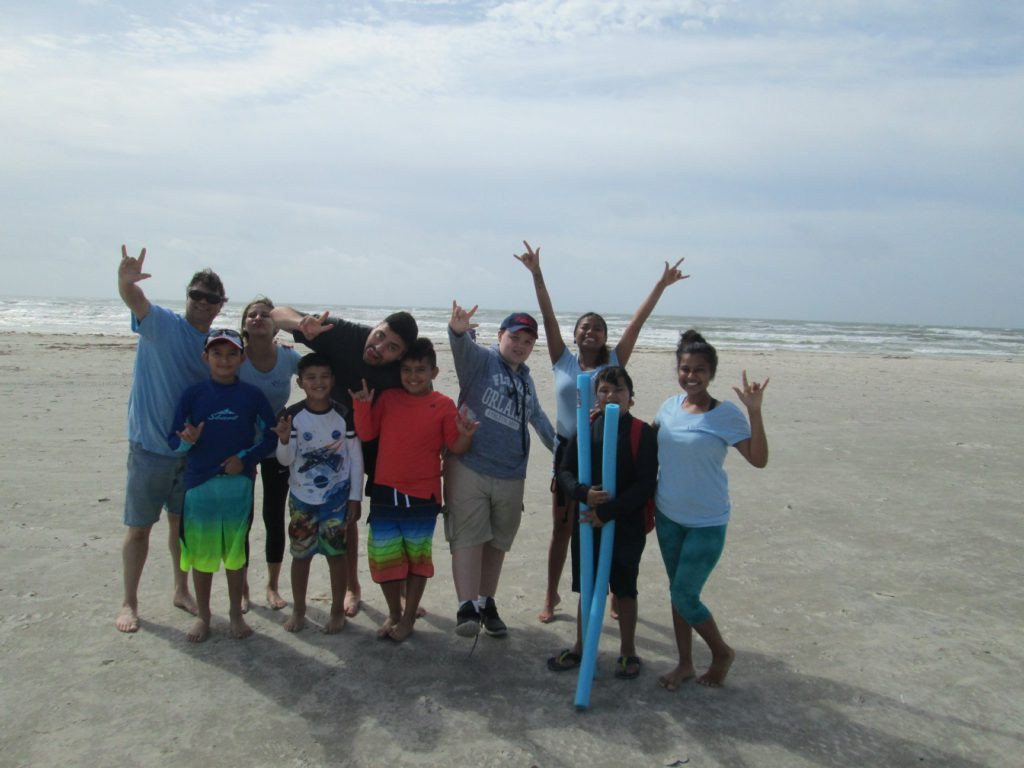 A group of kids and counselors smile at the camera while standing at the beach on a cloudy day.