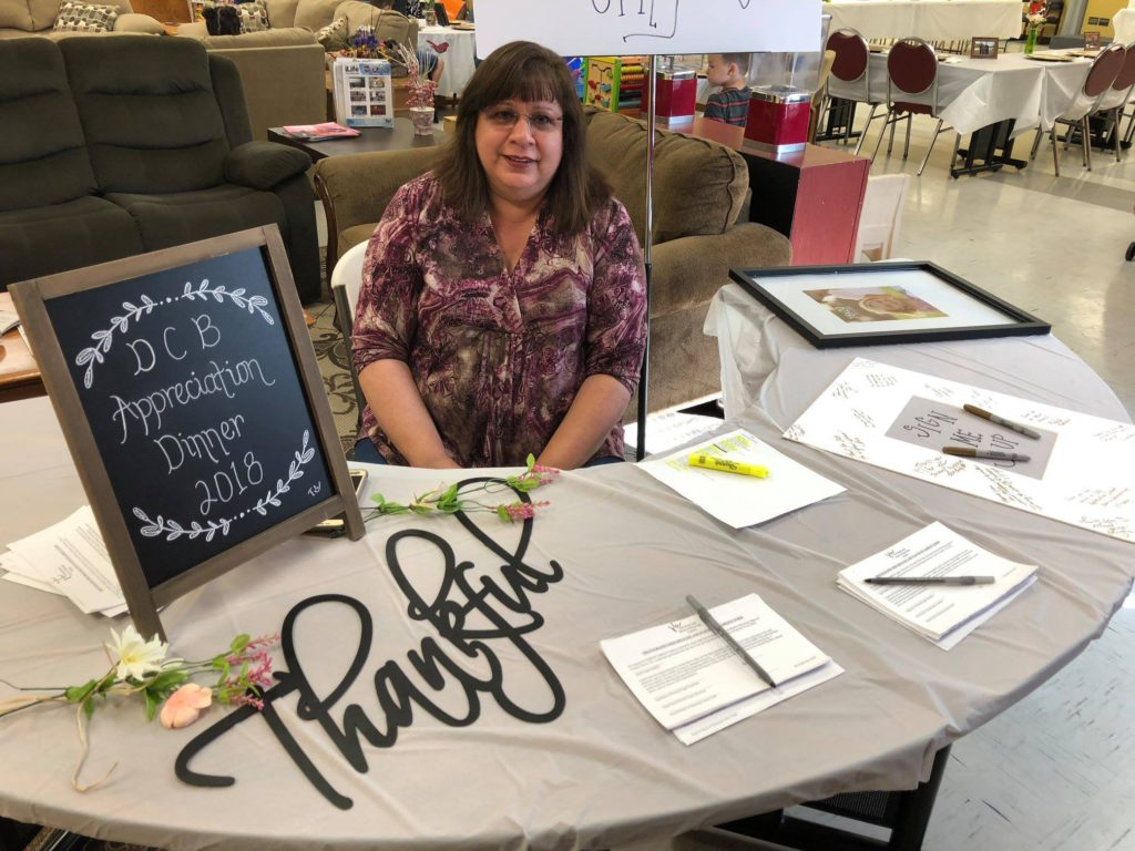 """A volunteer with brown hair and a purple/tan shirt sits at a table that has """"Thankful"""" and """"DCB Appreciation Dinner 2018"""" on it."""