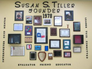 On a off-white/yellow wall, a collection of photos, awards, and words honor a founder who has since passed, Susan Tiller.