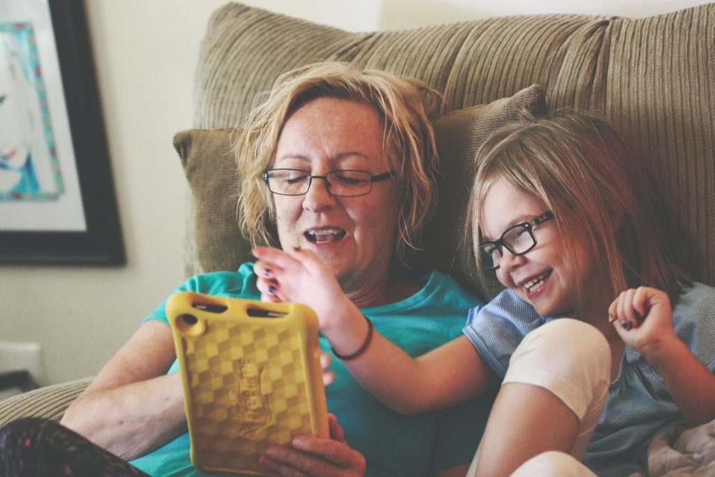 A light-skinned woman sits next to a young girl. Both are wearing glasses and acting friendly towards a tablet covered in a yellow case. They are sitting on a tan couch in a beige living room.